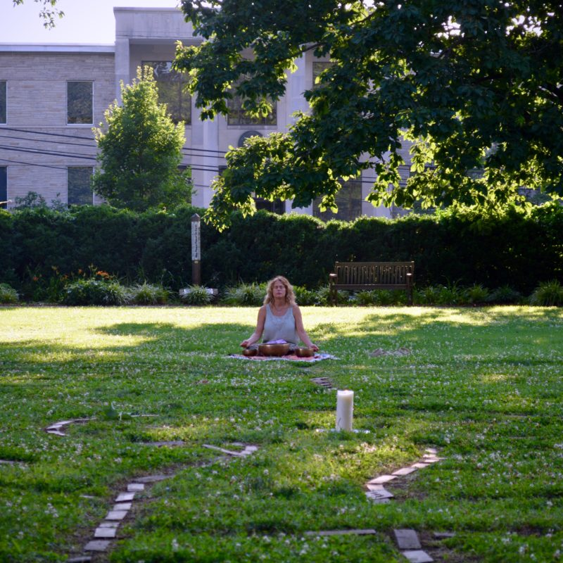 woman sitting on the egde of a labyrinth, meditating