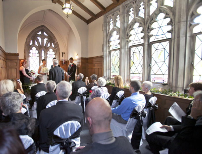 wedding ceremony in small chapel with bright windows and 10 guests