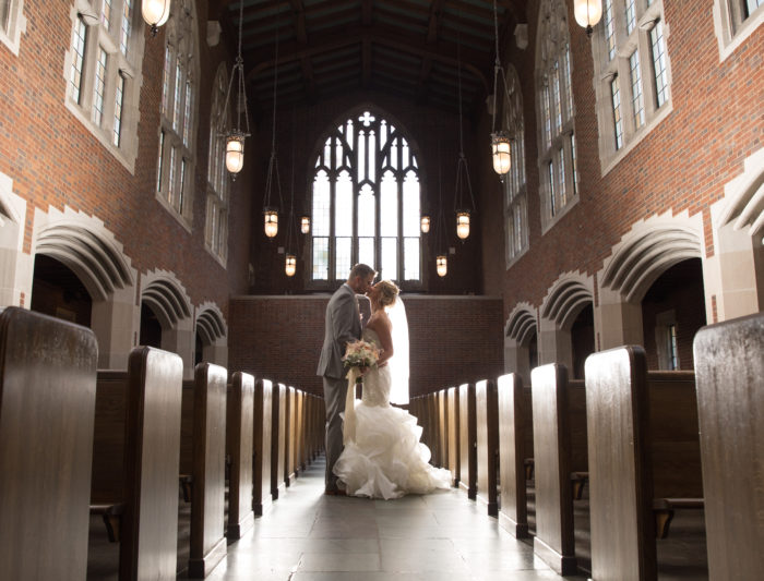 bride and groom kissing in large chapel with high ceilings
