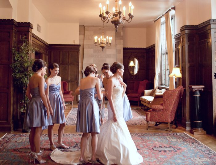 Bridesmaids fixing a bride's dress