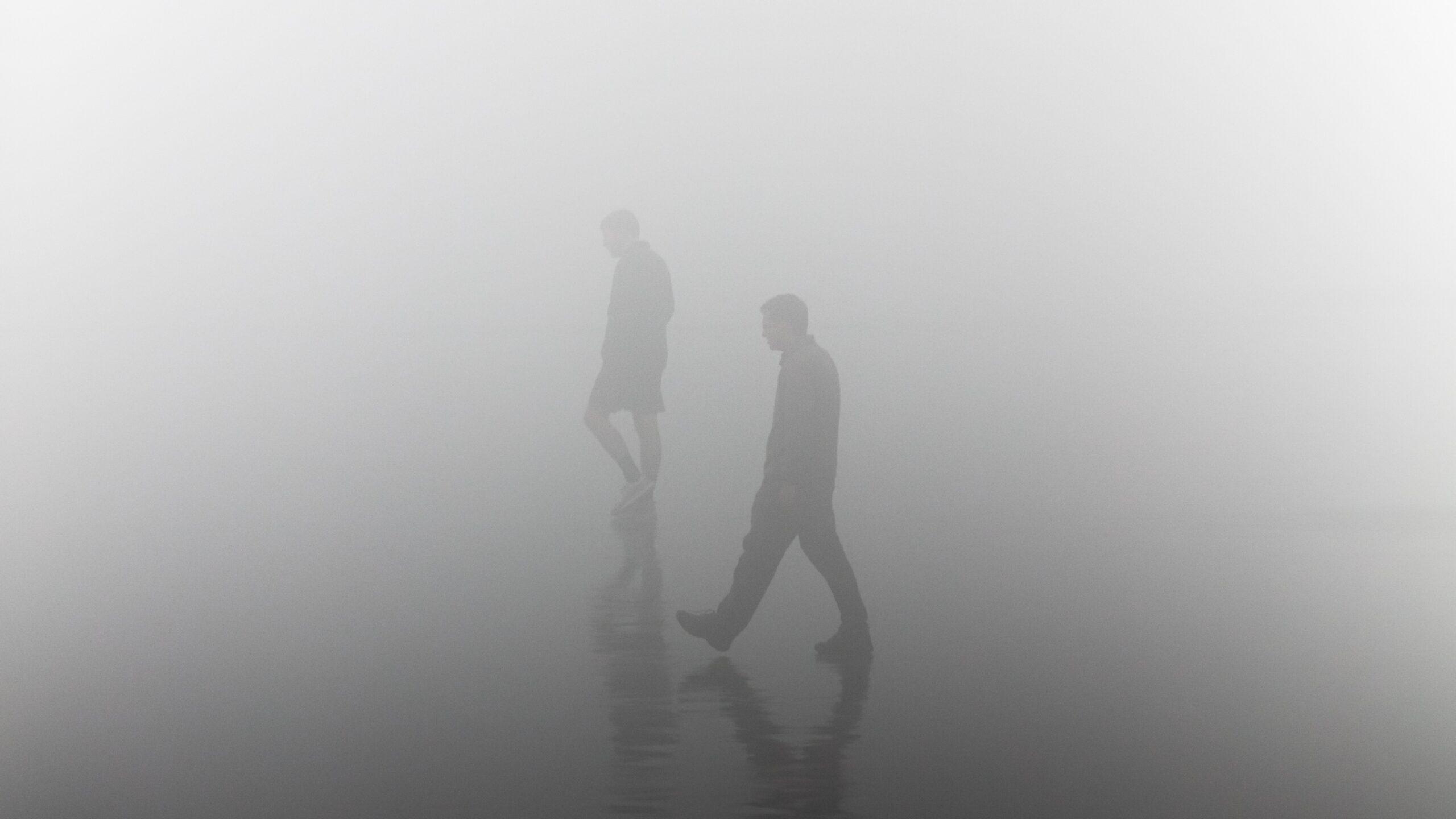 People walking through dense fog