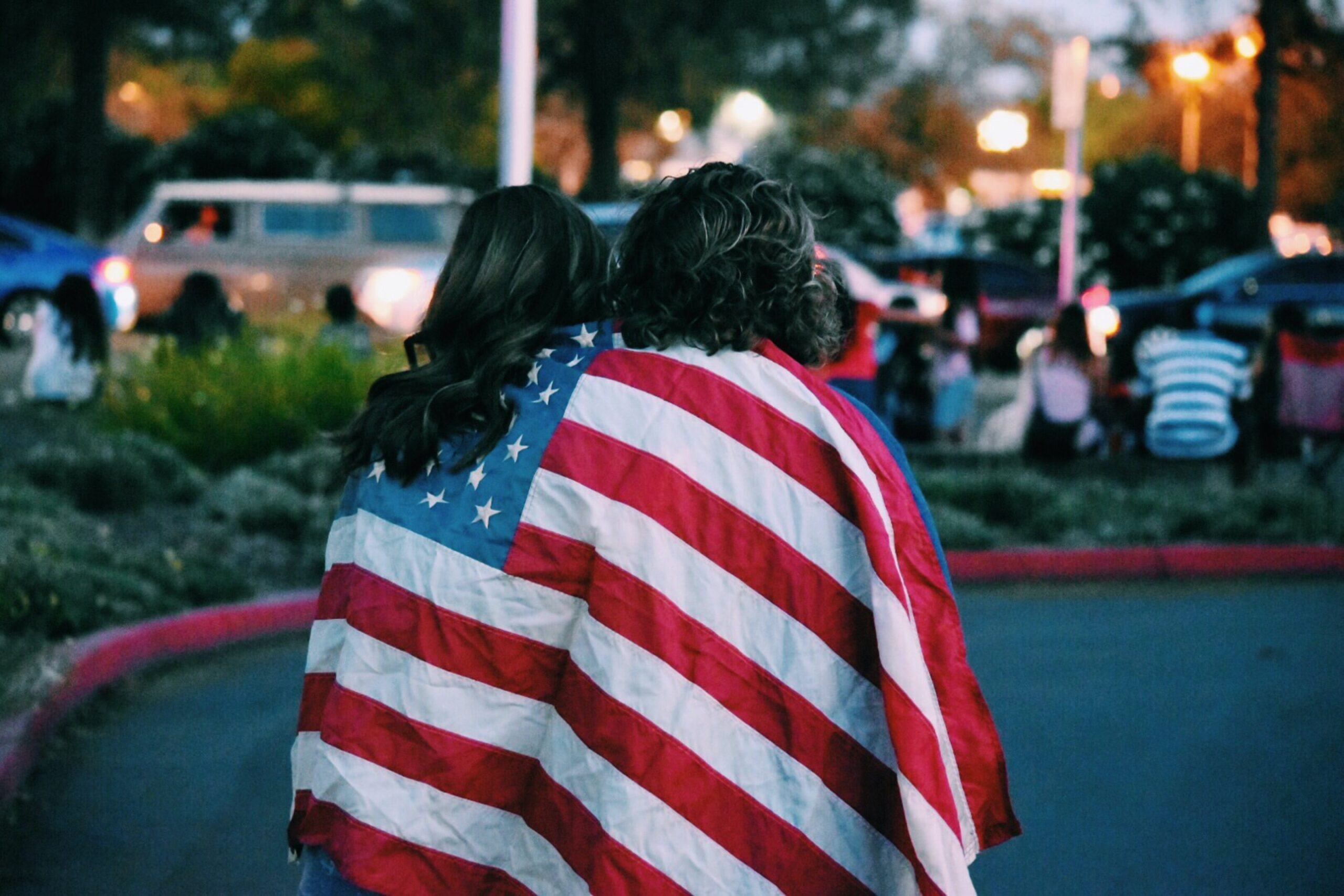 Two women embrace while draped in the American flag