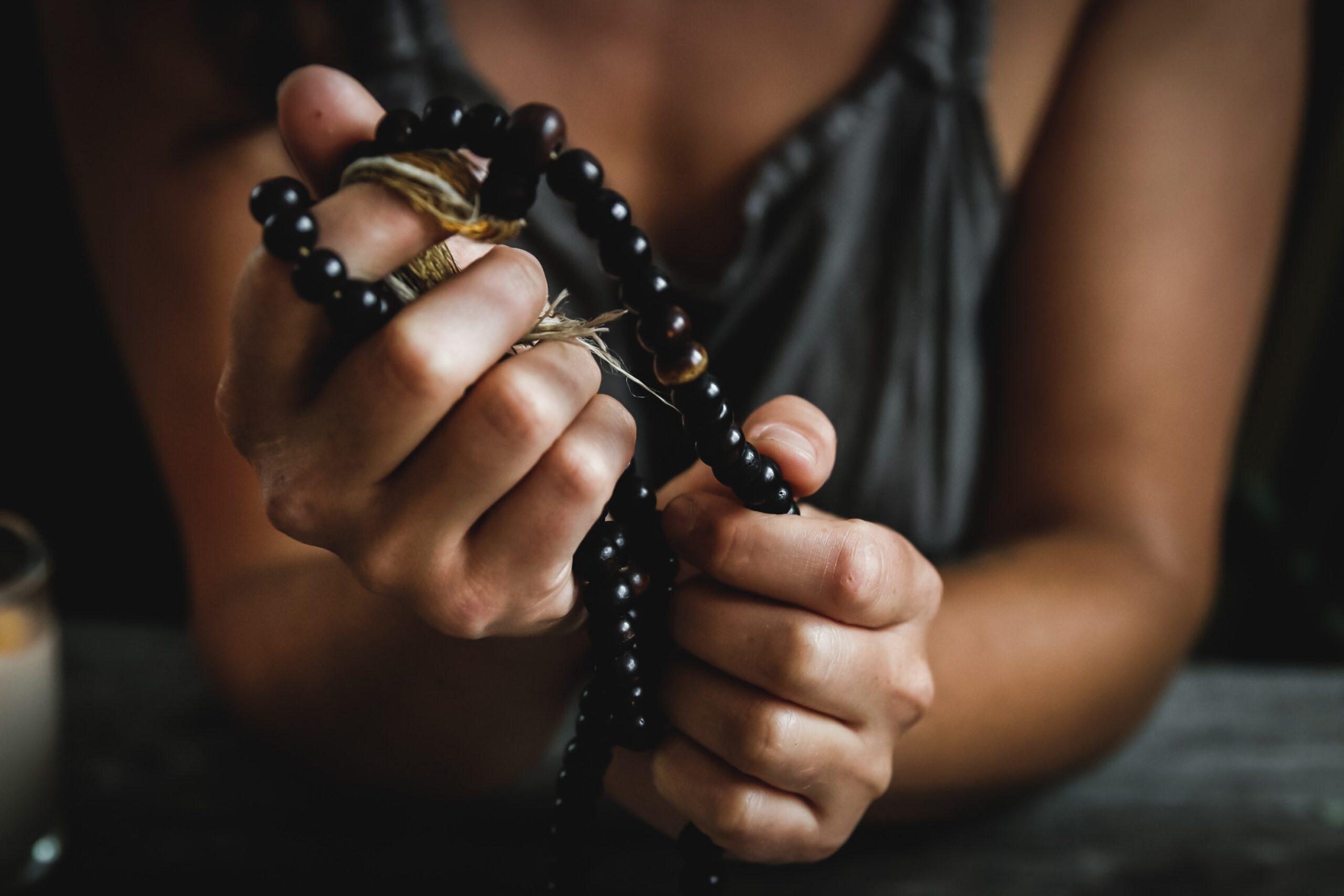 Person holding prayer beads